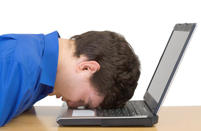 Man in despair buried head in computer keyboard